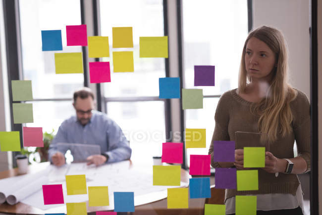 Female executive looking at sticky notes in office — Stock Photo