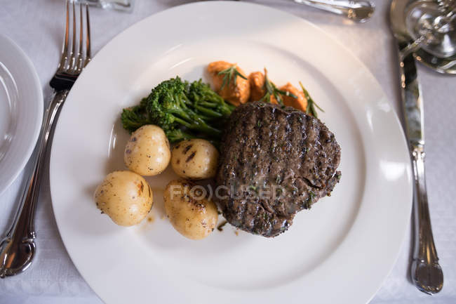 Close-up of beef steak served on plate with side dish on table — Stock Photo
