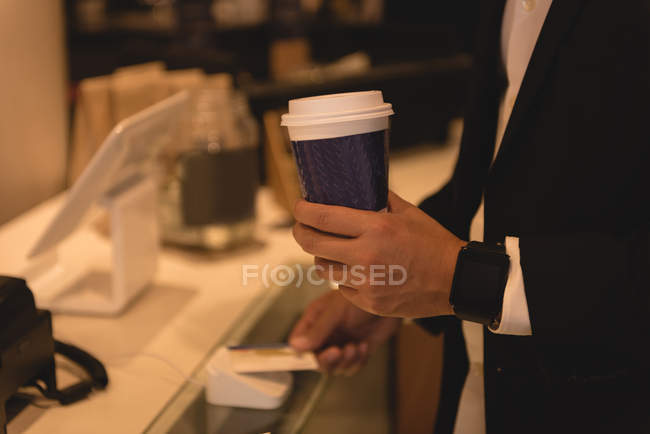 Mid section of businessman making NFC payment in coffee shop — Stock Photo