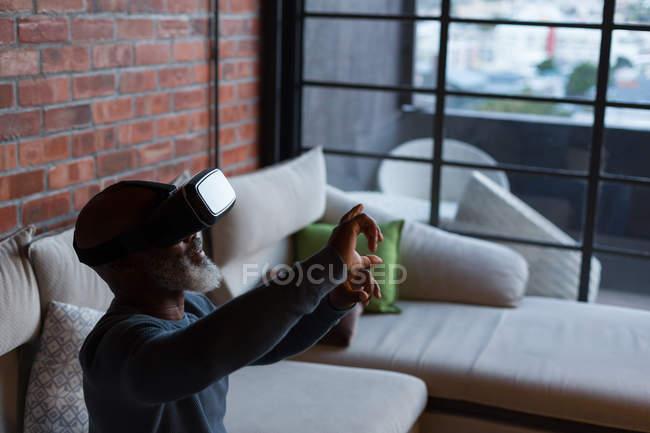 Senior man using virtual reality headset at home — Stock Photo
