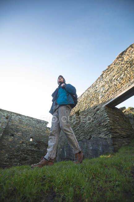 Молодой турист, прогуливающийся по старым руинам в сельской местности, с низким углом обзора — стоковое фото