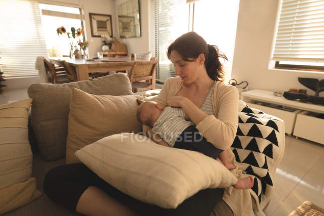 Young Mom Sitting On Sofa Breastfeeding Her Baby In Living Room At