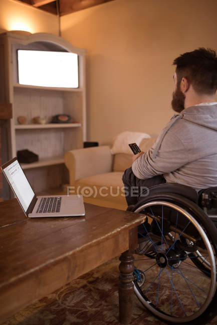 Homme handicapé regardant la télévision dans le salon à la maison — Photo de stock