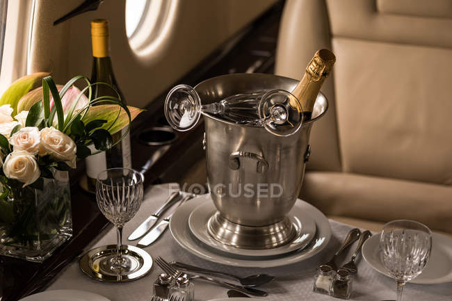 Champagne bottle with glass on a table in private jet — Stock Photo