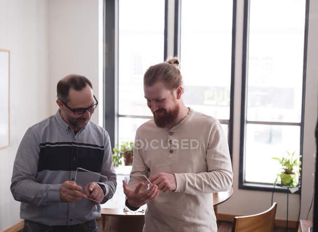 Коллеги по бизнесу используют стеклянный цифровой планшет в офисе — стоковое фото