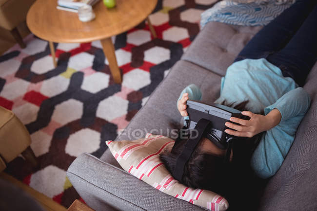 Woman using virtual reality headset in living room at home — Stock Photo
