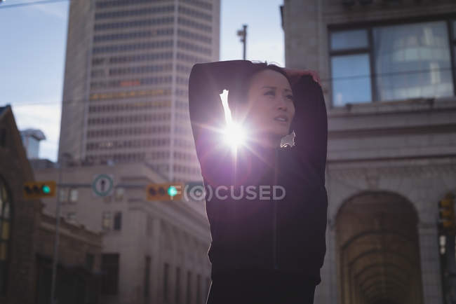 Fit woman warming up at street on a sunny day — Stock Photo