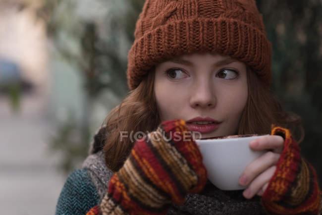 Femme en vêtements d'hiver ayant cappuccino dans un café en plein air — Photo de stock