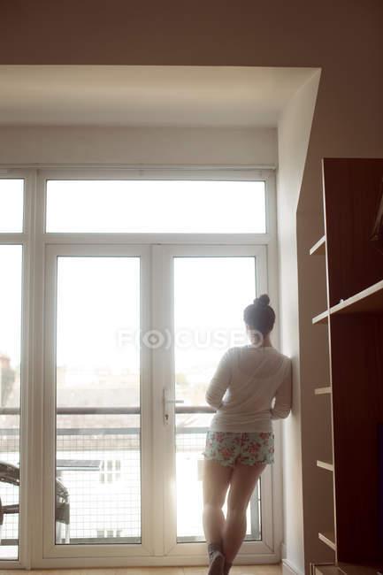 Вид сзади женщины, смотрящей в окно дома . — стоковое фото