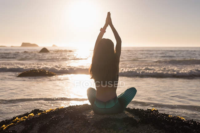 Fit woman performing yoga on rock in beach at dusk. — Stock Photo