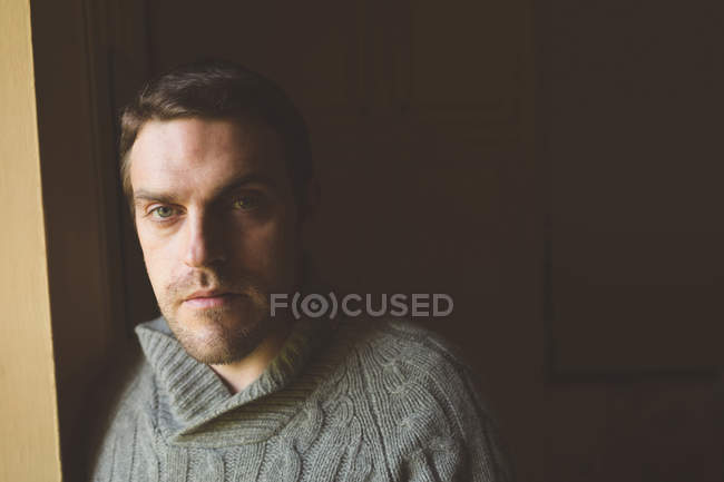Portrait of man standing near window at home — Stock Photo