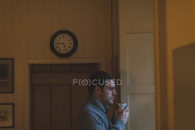 Un hombre pensativo tomando café en casa - foto de stock