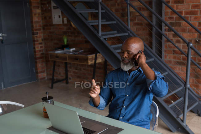 Active senior man talking on phone at home — Stock Photo