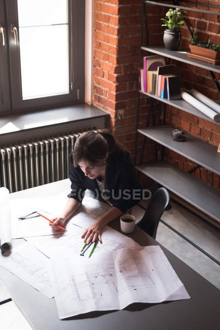Female executive working on blueprint in office — Stock Photo