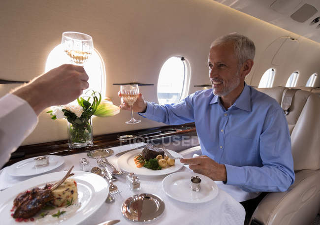 Happy business people toasting glasses of champagne in private jet — Stock Photo