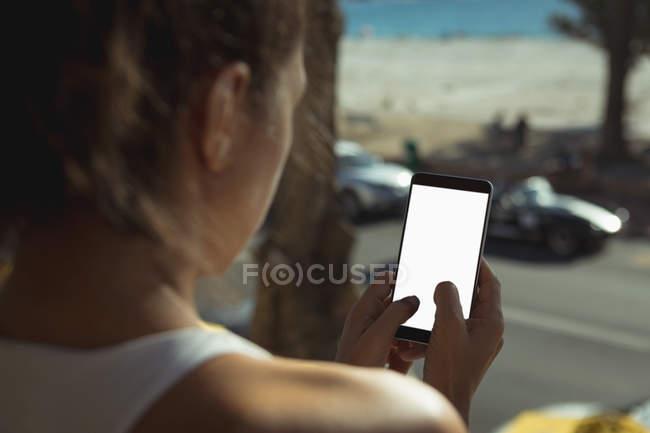 Visão traseira da mulher usando telefone celular em casa na frente da janela — Fotografia de Stock