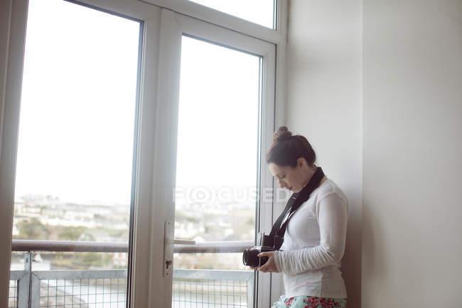 Mulher segurando câmera digital perto da janela em casa . — Fotografia de Stock
