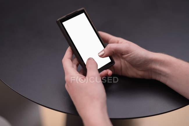 Mujer usando teléfono móvil en la mesa en la oficina - foto de stock