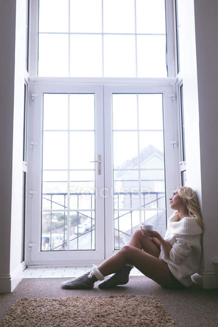 Задумчивая женщина пьет кофе у окна дома — стоковое фото