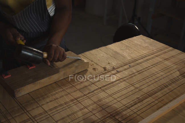 Mid section of carpenter carving wood at table in workshop — Stock Photo