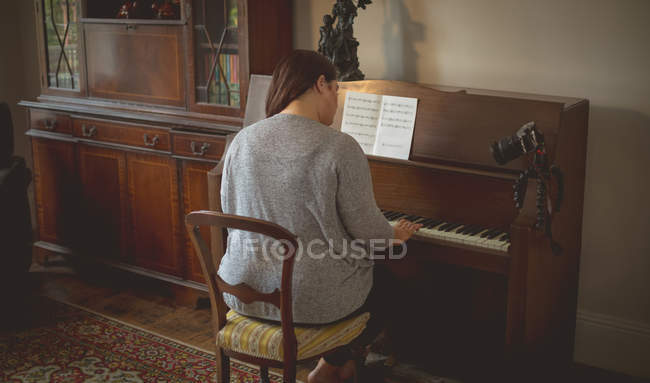 Rear view of female vlogger playing piano at home — Stock Photo
