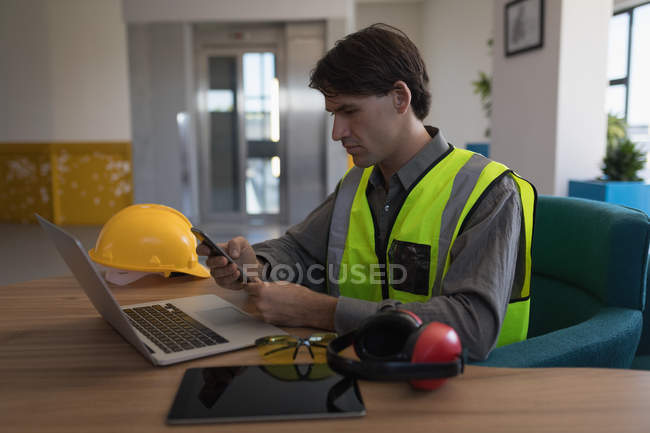 Male worker using mobile phone at desk in office — Stock Photo