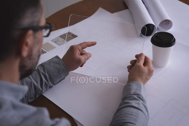 Male executive using glass digital tablet in office — Stock Photo