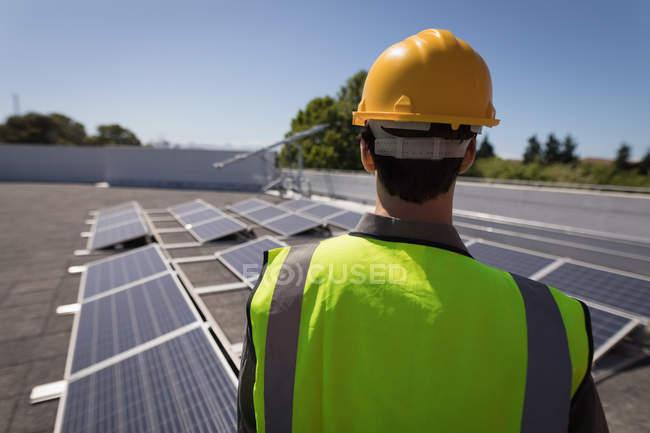 Vista trasera del trabajador masculino mirando el panel solar - foto de stock