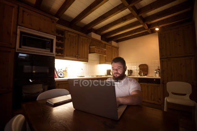 Disabled young man using laptop at home — Stock Photo