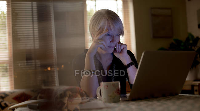 Продуманий зрілої жінки за допомогою ноутбука на дому — стокове фото