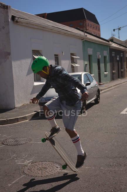 Mann tut Ollie Trick auf Skateboard in der Straße im Sonnenlicht — Stockfoto