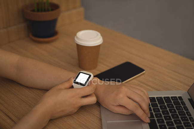 Businesswoman using smartwatch at desk in office — Stock Photo