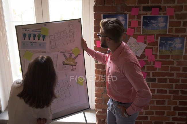 Male and female executives discussing over flip chart in office — Stock Photo