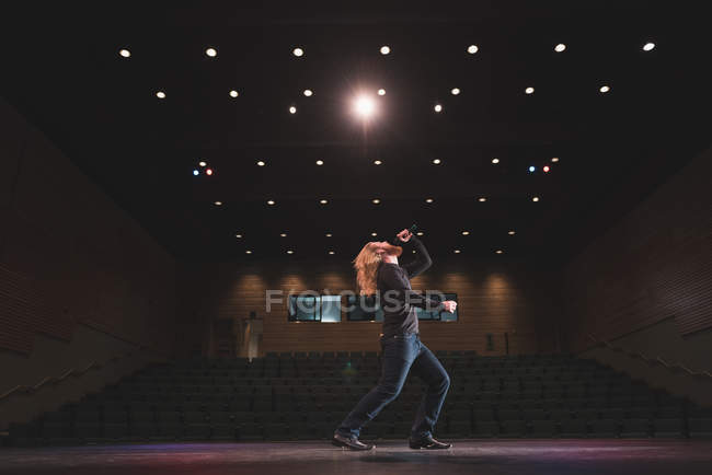 Male singer performing on stage at theatre. — Stock Photo