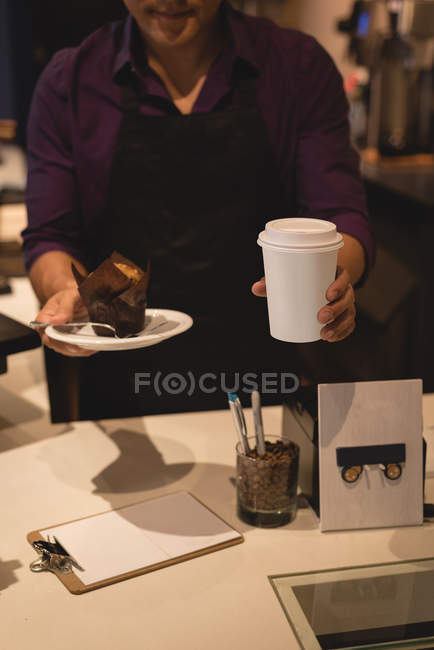 Waiter serving coffee and muffin in plate at coffee shop — Stock Photo