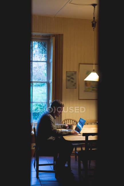 Homme attentif utilisant un ordinateur portable à la maison — Photo de stock