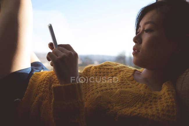 Женщина с мобильного телефона возле окна дома — стоковое фото