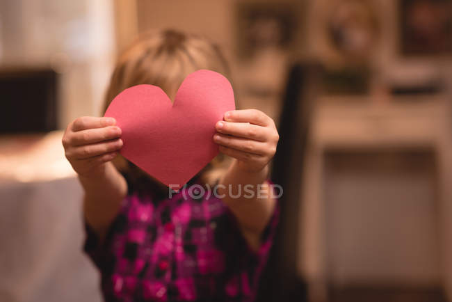 Girl holding heart shape decoration at home — Stock Photo
