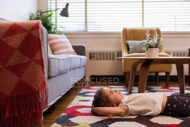 Fille réfléchie, couché sur le tapis dans le salon — Photo de stock