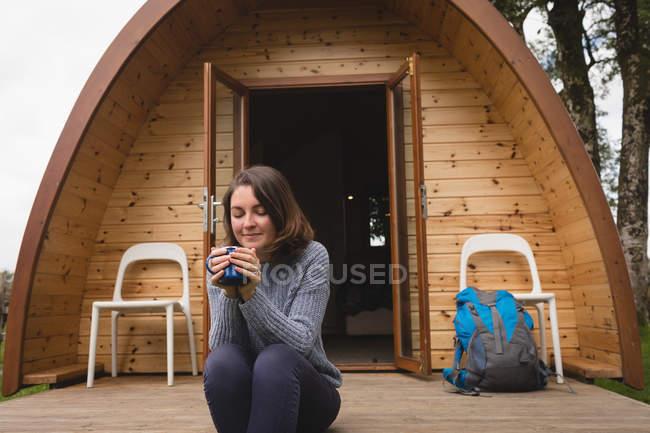 Красивая женщина, имея кофе вне кабины журнала — стоковое фото