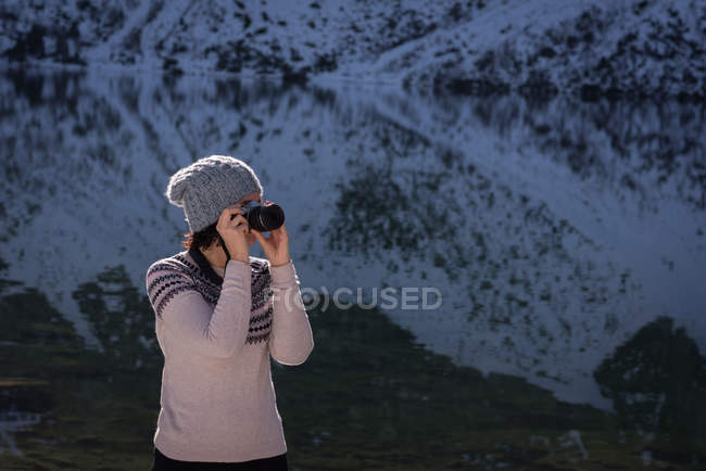 Female hiker taking photo with digital camera at lakeside — Stock Photo