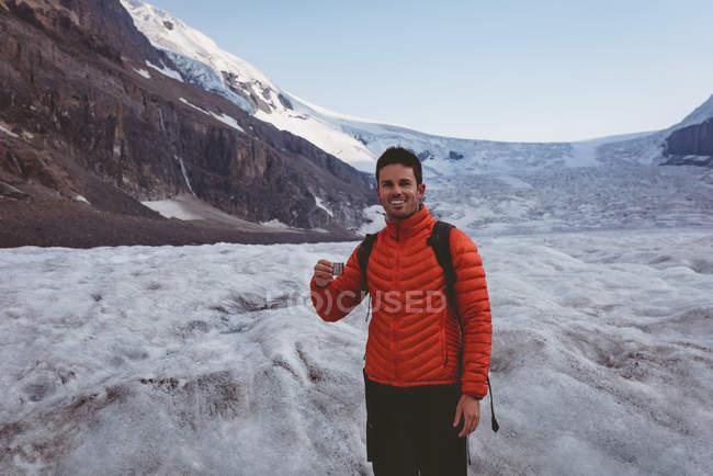 Männliche Wanderer halten kleine Tasse an einem sonnigen Tag im winter — Stockfoto