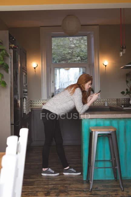 Seitenansicht einer Frau, die ihr Mobiltelefon zu Hause benutzt — Stockfoto