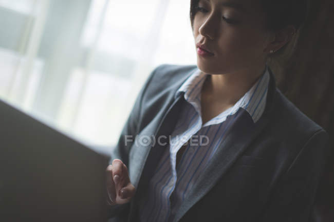 Close-up of businesswoman using laptop in hotel room — Stock Photo