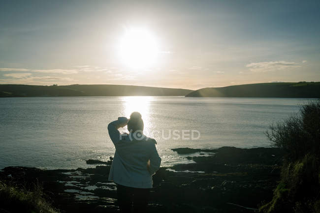Rear view of woman standing near riverside during sunset. — Stock Photo