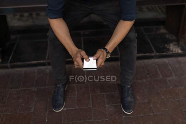 Низкая часть человека с помощью мобильного телефона на тротуар скамейке — стоковое фото