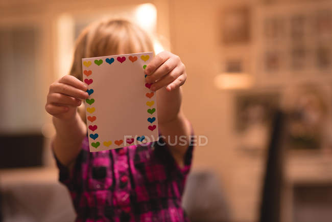 Girl holding heart shape valentine card at home — Stock Photo