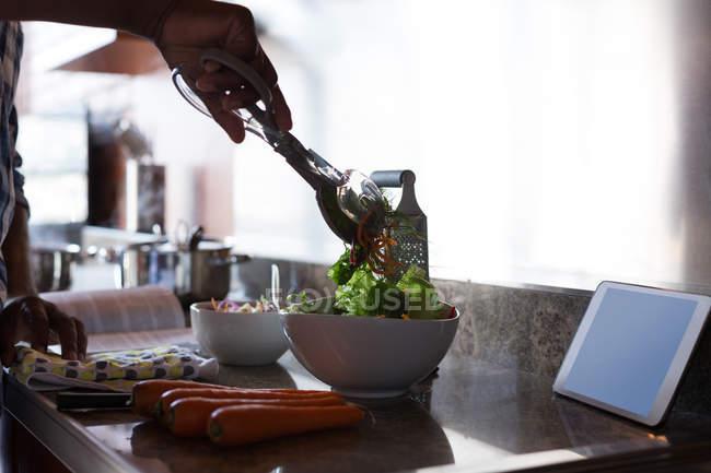Senior homme préparer salade dans la cuisine à la maison — Photo de stock