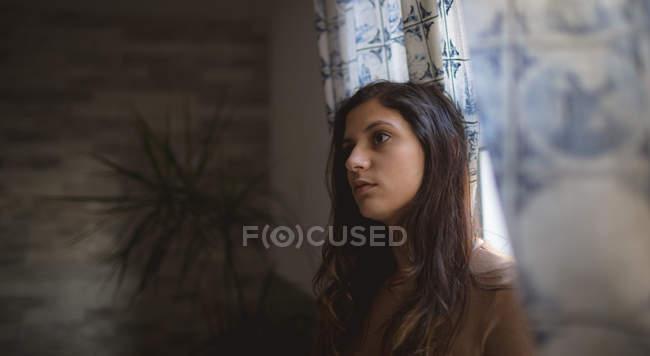 Nachdenkliche Frau sitzt zu Hause — Stockfoto