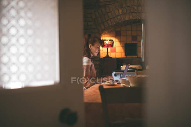 Donna che usa il computer portatile mentre fa colazione a casa — Foto stock